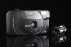 Analog automatic compact camera with 35mm film cassette isolated. Retro automatic film camera isolated on the black background stock photos