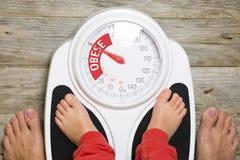Analog bathroom scale indicating child obesity stock images