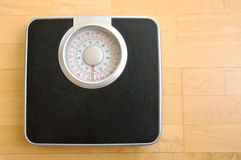 Analog black body weigh scale. With silver top dial on wood background Royalty Free Stock Photos