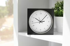 Analog clock on shelf indoors. Time of day stock image