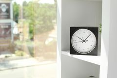 Analog clock on shelf indoors. Time of day royalty free stock photo