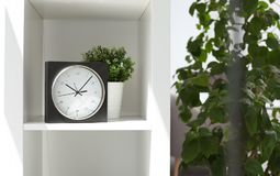 Analog clock on shelf indoors. Time of day stock photos