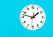 Analog clock on wall, with hour, minute and second hands. Analog clock on a wall, white clock face, cyan wall background. Copy space, very high resolution, clean royalty free stock photo