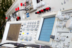 Analog and digital oscilloscope in the foreground. In the background measuring panel ready for measurements in electrical laboratory Royalty Free Stock Image