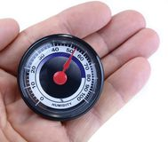 Analog humidity meter in the hand on white. Royalty Free Stock Images