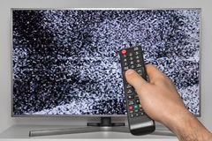 Analog noise on TV and human hand with TV remote control. Ler stock photo