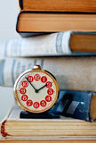 Analog retro alarm clock on a heap of old books Stock Photo