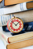 Analog retro alarm clock on a heap of old books Royalty Free Stock Images