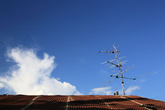 Analog tv antenna on roof with blue sky background Royalty Free Stock Photography
