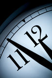 Analog wall clock in a low light with black hands and numbers with few minutes left to 12 hour Stock Photo
