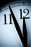 Analog wall clock in a low light with black hands and numbers with few minutes left to 12 hour Stock Image
