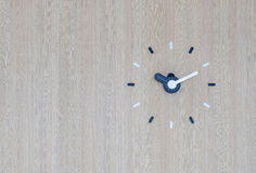 Analog wall clock on the wall. White and black analog wall clock on the wooden wall with copy space Royalty Free Stock Image