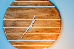 Analog wall clock. With white stripes on a wooden face. No digits were used in its construction Royalty Free Stock Photo