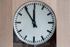 Analoge Uhr, die fünf bis zwölf lokalisiert auf Schwarzem zeigt Stockfotografie
