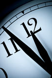 Analoge Wanduhr in einem Restlicht mit den schwarzen Händen und den Zahlen mit wenigen Minuten verließ bis 1/2-stündige Stunde Stockbild