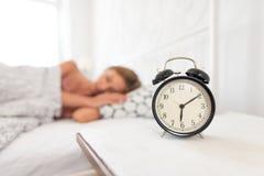 Analoge wekker De slaap van de vrouw in bed royalty-vrije stock afbeeldingen
