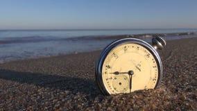Analoge zak uitstekende klok op het natte van het overzeese oceaanzand toevluchtstrand stock video