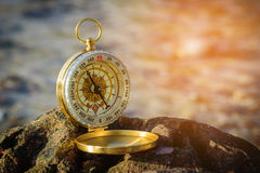 Analogical compass abandoned on the rocks with blurred sea backg Stock Images