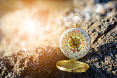 Analogical compass abandoned on the rocks with blurred sea Royalty Free Stock Image