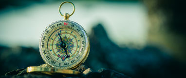 Analogical compass abandoned on the rocks with blurred sea Royalty Free Stock Images