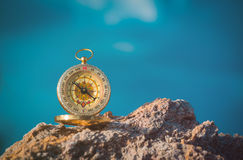 Analogical compass abandoned on the rocks with blurred sea Royalty Free Stock Photography