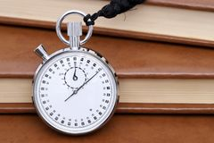Analogue metal stopwatch. With old books background Royalty Free Stock Photography