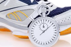 Analogue metal stopwatch. Analogue stopwatch with sport running shoes on white background Royalty Free Stock Images