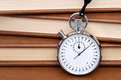 Analogue metal stopwatch. With old books background stock photography