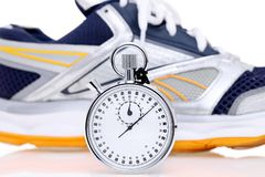 Analogue metal stopwatch. Analogue stopwatch with sport running shoes on white background Royalty Free Stock Photos