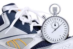 Analogue metal stopwatch. Analogue stopwatch with sport running shoes on white background Royalty Free Stock Photo