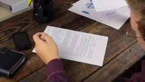 Analysant les diagrammes, l'homme d'affaires a signé le stylo bille de contrat banque de vidéos