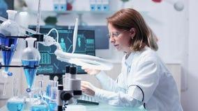 Analyse de femme de chimiste un échantillon utilisant une grande loupe banque de vidéos
