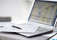 Analyse des diagrammes d'investissement avec l'ordinateur portable Photos libres de droits