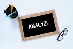 Analyseer - ge?soleerd woord in hoogste mening van bord De zaken analyseren om doel te krijgen Glazen, teller en pengeval stock foto
