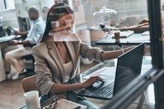 analysering av data Bästa sikt av den moderna unga kvinnan som använder datorwh royaltyfri foto