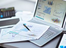 Analysering av investeringdiagram med bärbara datorn Fotografering för Bildbyråer
