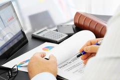 Analysieren von Finanzdokumenten im Büro Lizenzfreies Stockfoto