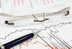 Stocks and shares report. Glasses and pen used in statistical analysis of a stocks and shares chart Stock Photo