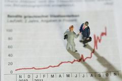 Analysing Annual Monthly Statistics. Two miniature figurines of businessmen having a meeting alongside a fluctuating red line graph showing improving Stock Photos