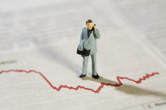 Analysing Business Statistics. A miniature model businessman stands over a red line graph talking on his mobile phone Stock Photos