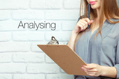 Analysing. Businesswoman with clipboard and pen making notes and standing near text - analysing royalty free stock photo