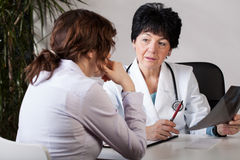 Analysing examination outcome. A patient and a doctor analyzing the outcome of an examination Royalty Free Stock Photos