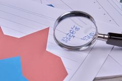 Analysing financial data with a magnifying glass. royalty free stock photography