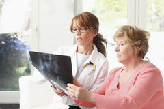 Analysing x-ray. Female doctor analysing x-ray with senior patient at small clinic Stock Photography