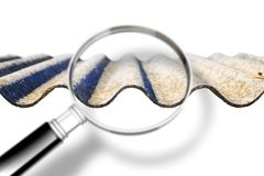 Analysis of the compounds of a dangerous asbestos roof - concept image with magnifying glass.  stock photography