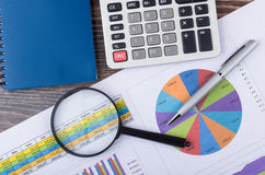Analysis printouts with table and chart, calculator and pen Royalty Free Stock Photo