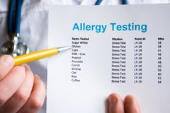 Analysis and testing for allergies photo concept. Doctor points with pen in his hand on result of patient allergy test in foregrou. Nd, standing in medical gown royalty free stock image