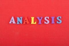 ANALYSord på röd bakgrund som komponeras från träbokstäver för färgrikt abc-alfabetkvarter, kopieringsutrymme för annonstext enge royaltyfri foto