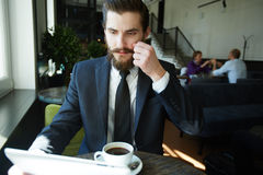 Analyst in cafe. Contemporary salesman looking through online data in tablet royalty free stock photo