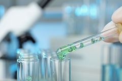 Analyst dripping reagent into test tube with sample stock images